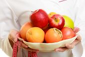 foto of recommendation  - Closeup woman in white lab coat holding fruits and colorful measure tapes isolated - JPG