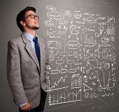 foto of anal  - Attractive young man looking at stock market graphs and symbols - JPG
