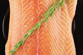 foto of fresh water fish  - raw fresh uncooked salmon red fish fillet on black plate with rosemary twig isolated over white background - JPG
