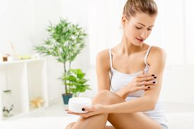 picture of body-lotion  - Beautiful blonde young woman applying body lotion - JPG