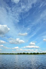image of kama  - Idyllic summer landscape with river and cloudy sky and trace of the plane - JPG