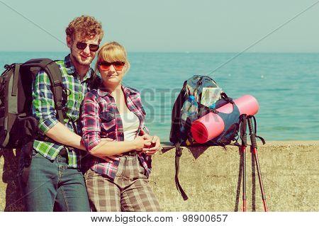 Couple Backpacker Tramping By Seaside