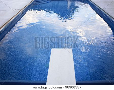 a local public pool without any people in it with a diving board and reflections of clouds