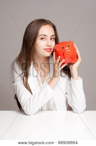 Gorgeous Brunette Woman Holding Piggy Bank.
