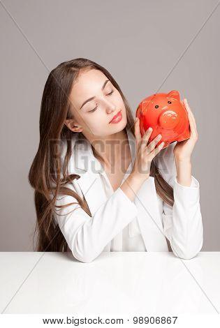 Brunette Beauty With Orange Piggy Bank.