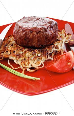 grilled beef fillet pieces on noodles , red hot chili pepper and tomato on red plate isolated over white background