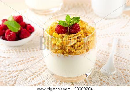 Breakfast with cereal flakes, yogurt and fresh raspberries