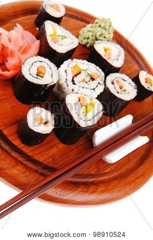 Maki Sushi : Maki Rolls and California rolls made of fresh raw Salmon(sake), Tuna(maguro) and Eel(unagi) . on wooden plate with wasabi and ginger isolated over white background