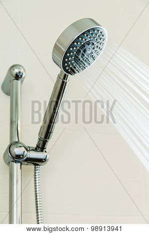 Silver shower head in bathroom with water drops flowing, Bathroom equipment.
