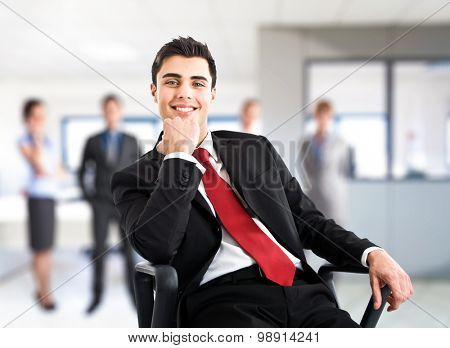 Young businessman smiling while sitting on his chair