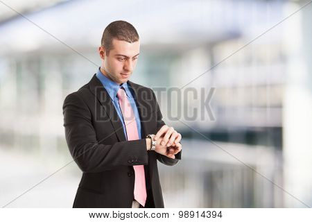 Young businessman checking time on his watch