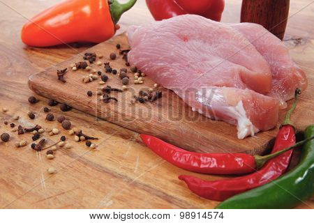 fresh raw turkey meat steak with hot sweet pepper dry spices castor and pepperbox on wood cutting boar over table