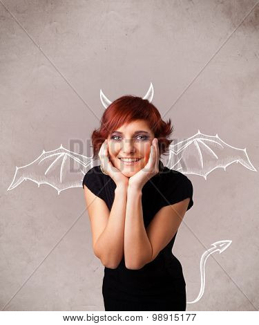 Young nasty girl with devil horns and wings drawing