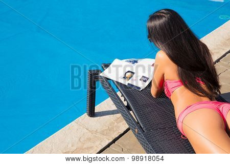Young girl lying on deckchair and reading magazine near swim pool outdoors