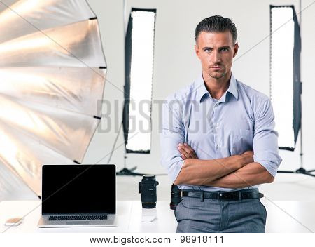 Portrait of a confident businessman standing with arms folded in studio