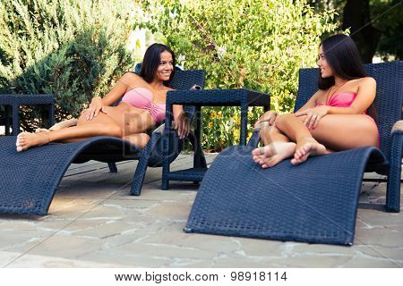 Two beautiful girls talking on the deckchair outdoors