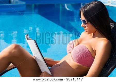 Portrait of a beautiful woman lying on deckchair near swim pool and reading magazine outdoors