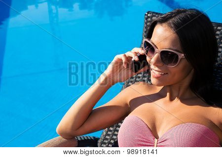 Smiling pretty woman talking on the phone on deckchair outdoors
