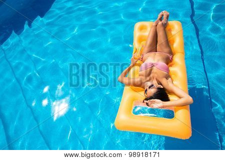 Young girl resting on air mattress in the swimming pool