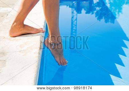Closeup portrait of female legs near swim pool