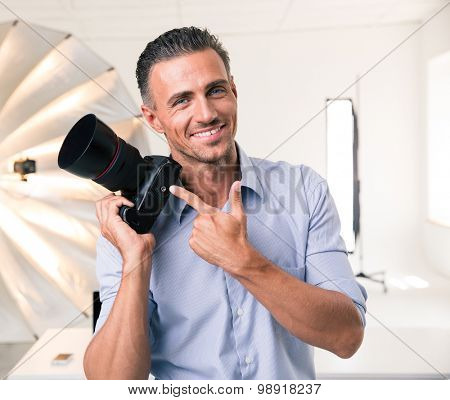 Portrait of a smiling photographer pointing finger at camera in studio