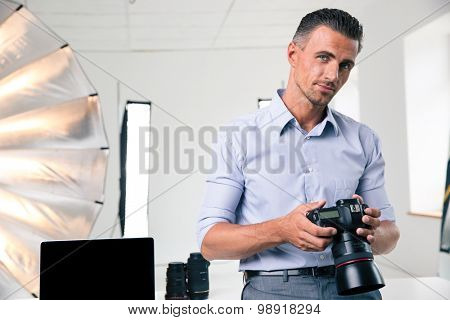 Portrait of a handsome man holding camera and looking at camera in studio