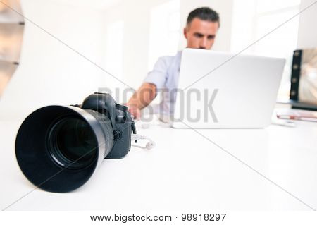 Closeup portrait of a young man using laptop. Focus on camera