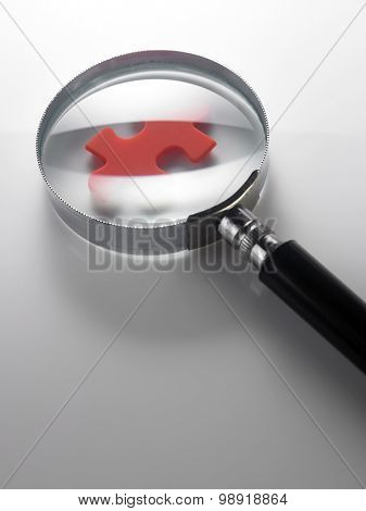 magnifying glass on the piece of  puzzle