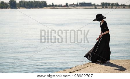 Ballerina In Hat And Long Black Dress Dancing On Riverbank.