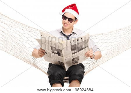 Young guy with Santa hat sitting in a hammock and reading a newspaper.The newspaper is custom made, text is Latin and the pictures are my copyright. Additionally property release uploaded.
