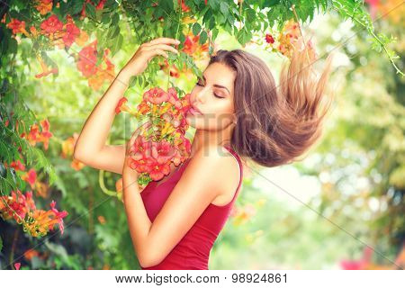 Beauty model girl enjoying nature in garden with beautiful tropical flowers. Young woman smelling flowers outdoors