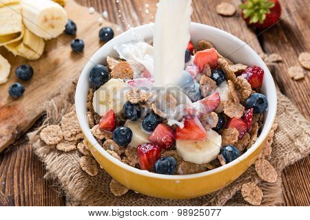 Pouring Milk On Cornflakes With Fresh Fruits