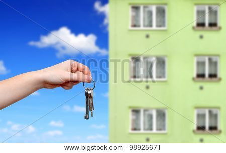Hand with keys in the background apartment building