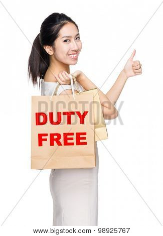 Woman with thumb up gesture and holding shopping bag for showing duty free