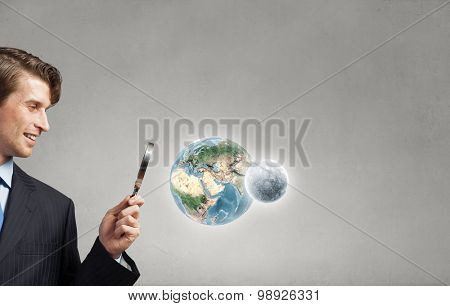 Young smiling man looking in magnifying glass. Elements of this image are furnished by NASA