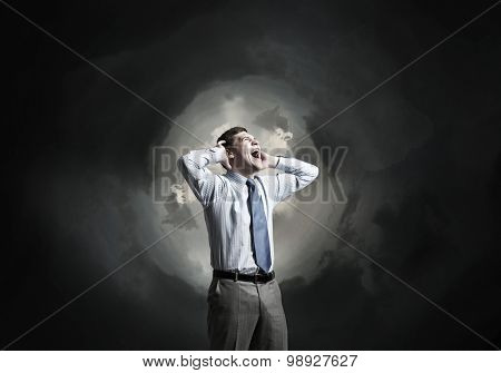Frustrated businessman screaming and covering his ears with hands