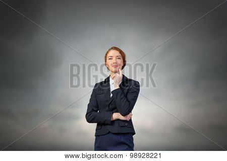 Young thoughtful businesswoman with finger on chin