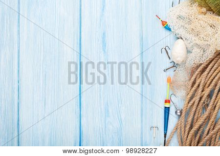 Fishing equipment on blue wooden table. Top view with copy space