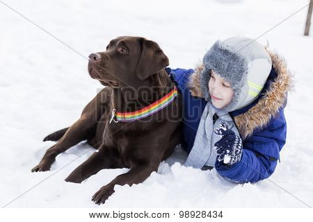 Kid of school age with dog in winter park