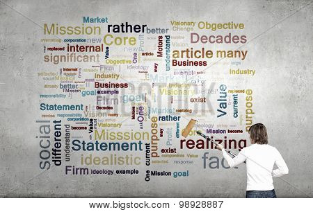 Young businessman standing with back and painting different words on wall