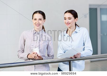 Two women standing at balcony and having dialogue