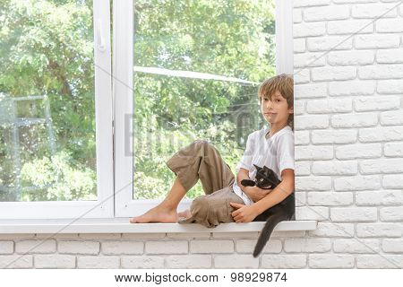 indoor portrait of young happy smiing child boy with little black cat sitting near window at home