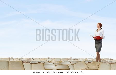 Pretty businesswoman walking on pile of old books