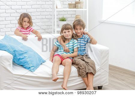 indoor portrait of young happy smiing children, kids, boy and girls, sitting on sofa at home