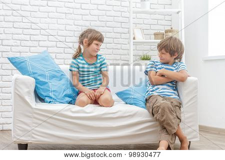 indoor portrait of young happy smiing children, kids, boy and girl, sitting on sofa at home