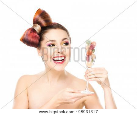 Beautiful smiling woman holding a wineglass with candies.