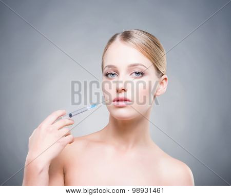 Young woman with syringe injecting botox into smooth skin.