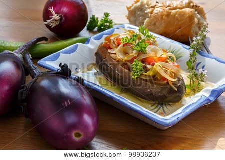 Imam Bayildi. Eggplants stuffed with vegetables on square plate.
