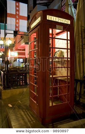 British red street telephone cabine with pub background