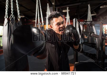 young aggressive businessman training shadow boxing at gym with gloves throwing vicious punch in ang